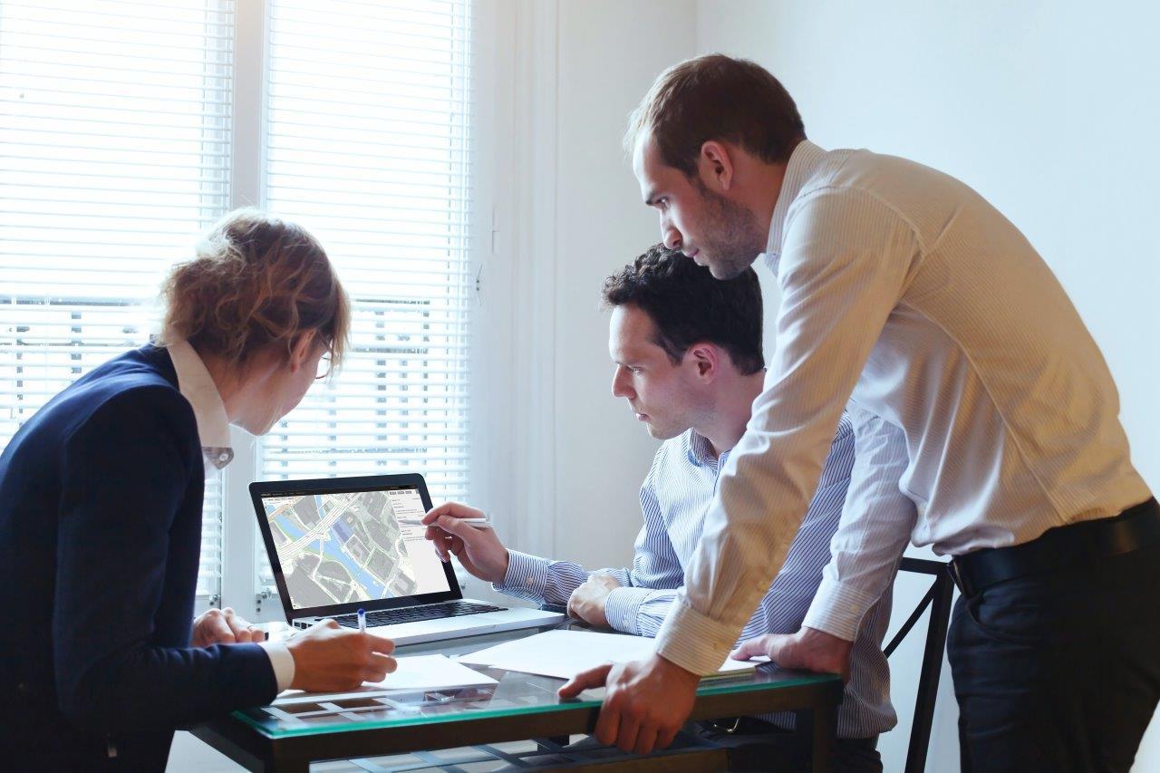 Tre personer foran PC med kart